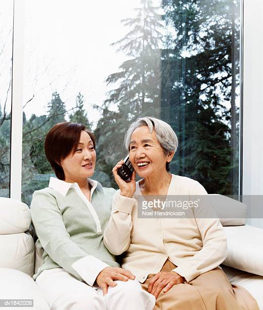 Senior Woman Sits Next to Her Daughter on a Sofa, Talking on the Phone
