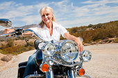Senior woman sits on motorcycle on desert road