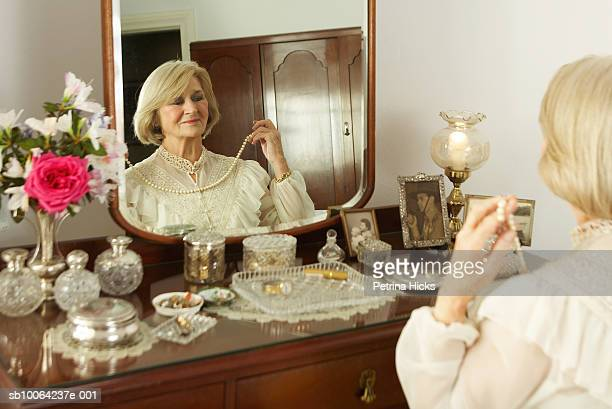 Senior woman sitting at dressing table, trying on necklace