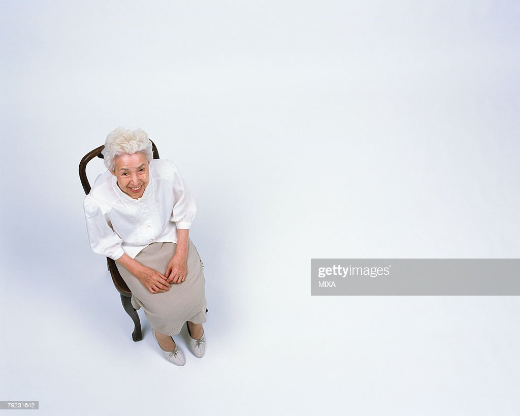 A senior woman sitting in a chair : Stock Photo