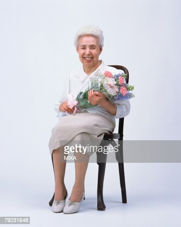 A senior woman sitting in a chair with flower bouquet : Stock Photo