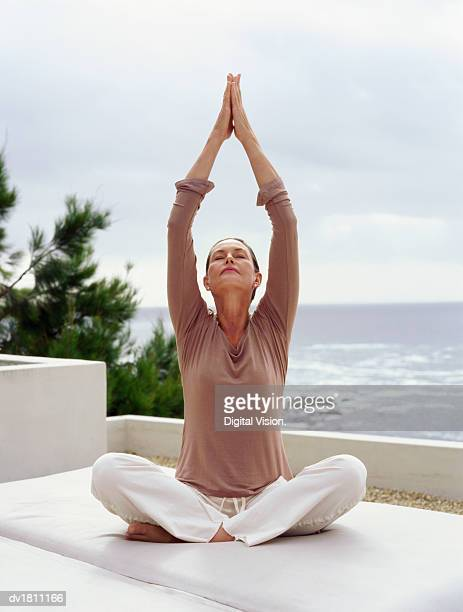 Senior Woman Sitting in a Cross Legged Yoga Position with the Sea in the Background