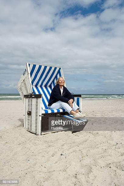 A senior woman sitting in a hooded beach chair