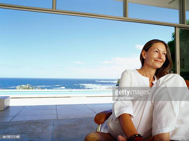 Senior Woman Sitting in a Modern Room with Open Patio Doors with the Sea in the Background