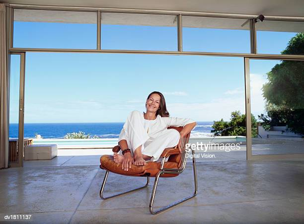 Senior Woman Sitting in a Modern Room with the Sea in the Background