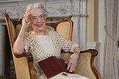 Senior woman sitting in armchair, smiling, portrait