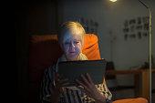 Senior woman sitting in armchair using digital tablet