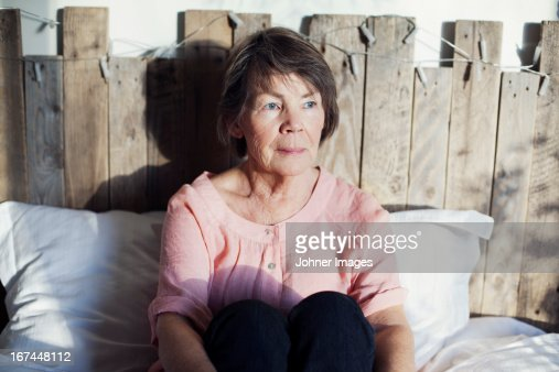 Senior woman sitting in bed : Stock Photo