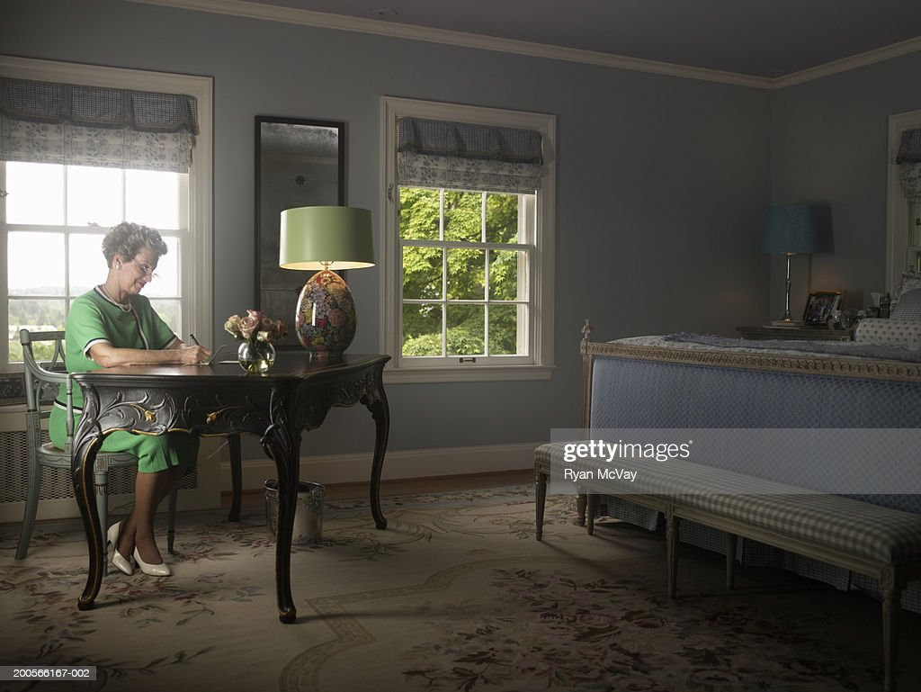 Senior woman sitting in bedroom writing at desk : Stock Photo