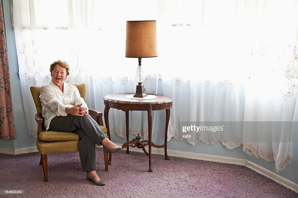 Senior woman sitting in chair at home : Stock Photo