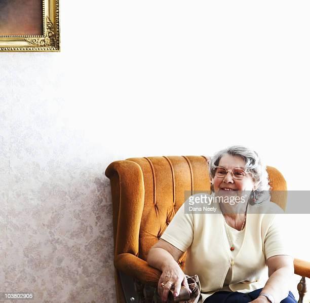 Senior woman sitting in chair, portrait.