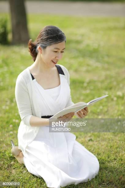 Senior woman sitting in grass reading book