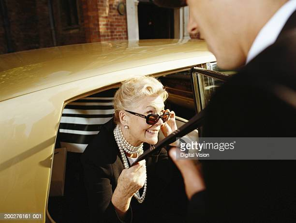 Senior woman sitting in limousine, holding man's tie, smiling