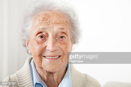 Senior woman sitting on a bench and looking into camera