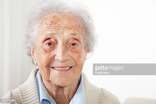 Senior Frau sitzt auf einer Bank und Blick in die Kamera