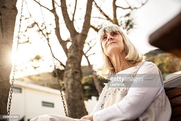 Senior woman sitting on a bench on the backyard