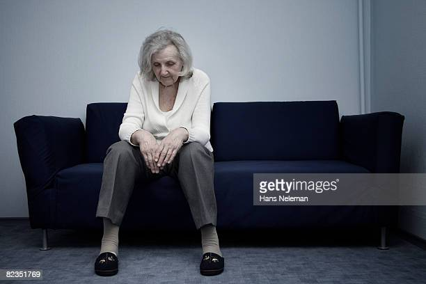 Senior woman sitting on a couch and thinking