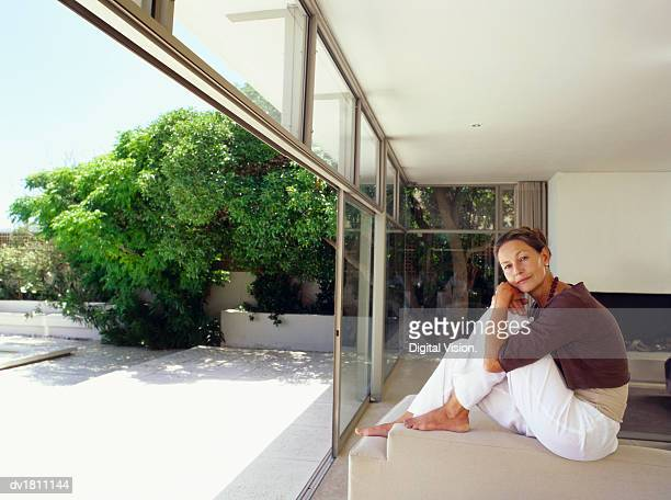 Senior Woman Sitting on a Sofa in a Showcase Home With Open French Windows Leading to a Garden