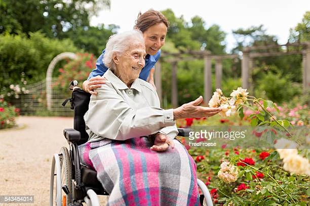 Senior woman sitting on a wheelchair with caregiver