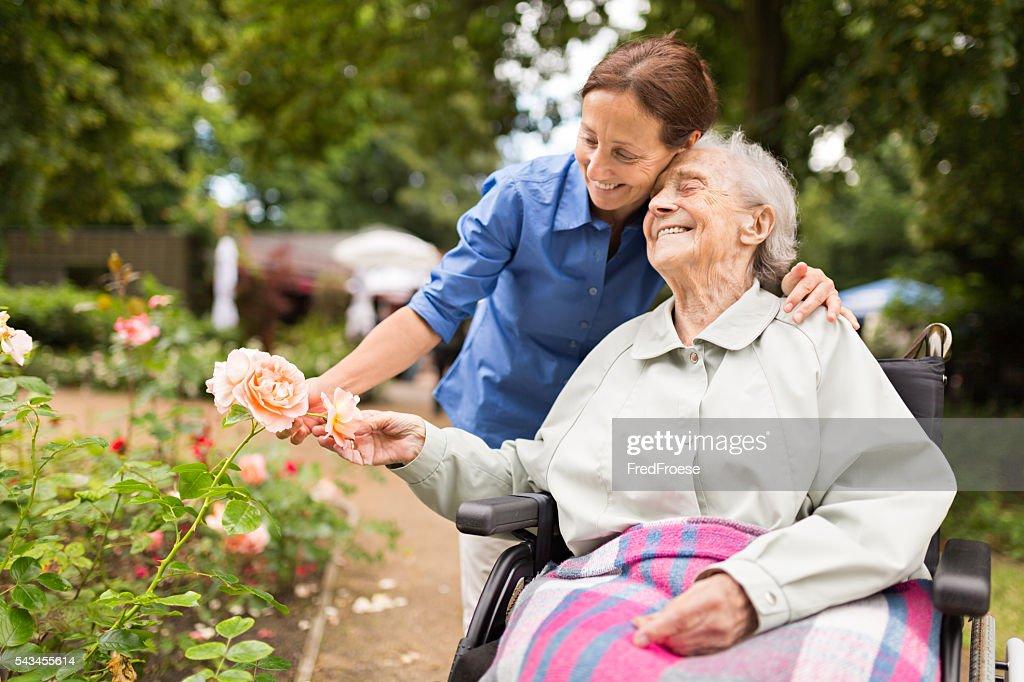 Senior Frau sitzt auf einem Rollstuhl mit Der Fürsorgliche : Stock-Foto