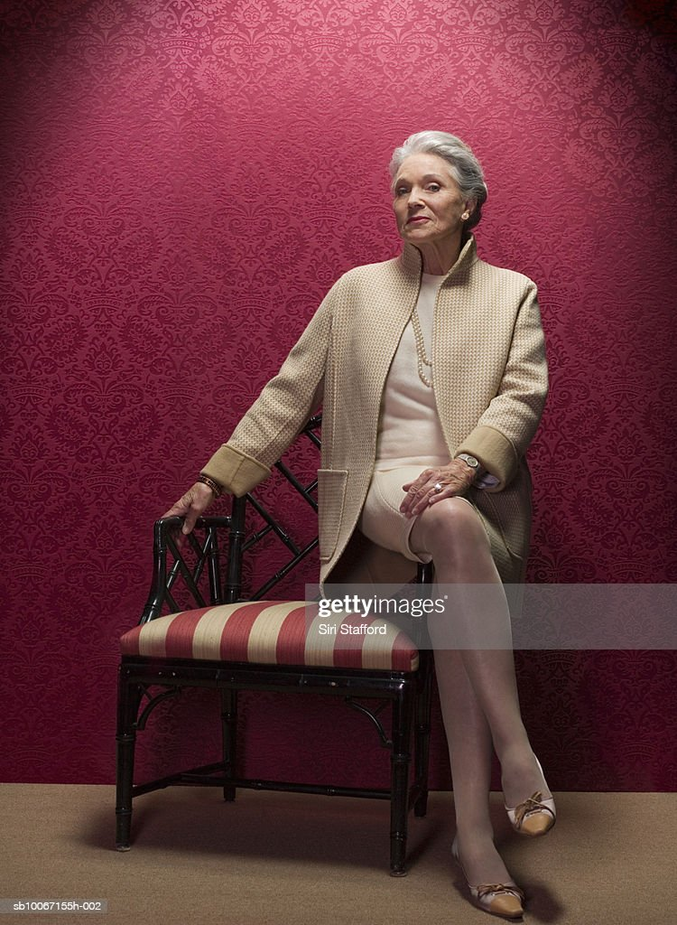 Senior woman sitting on antique chair, portrait
