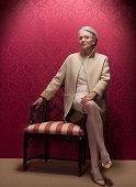 Senior woman sitting on antique chair, portrait