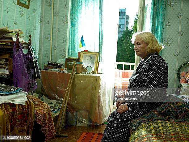 Senior woman sitting on bed, looking down