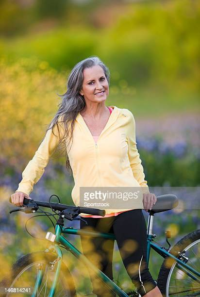 Senior Woman Sitting On Bicycle In Bluebonnet Field