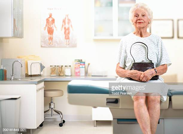 Senior woman sitting on examination table in doctor's office, portrait