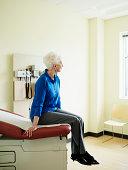 Senior woman sitting on examination table, looking away