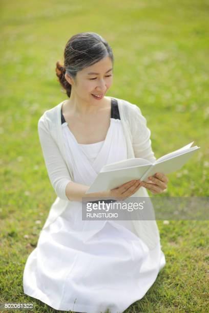 Senior Woman Sitting On Grass, Reading Book