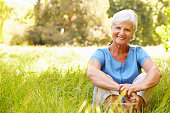 Senior woman sitting on grass relaxing, smiling to camera