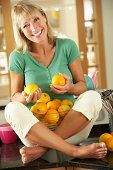 Senior Woman Sitting On Kitchen Counter With Bowl Of Oranges