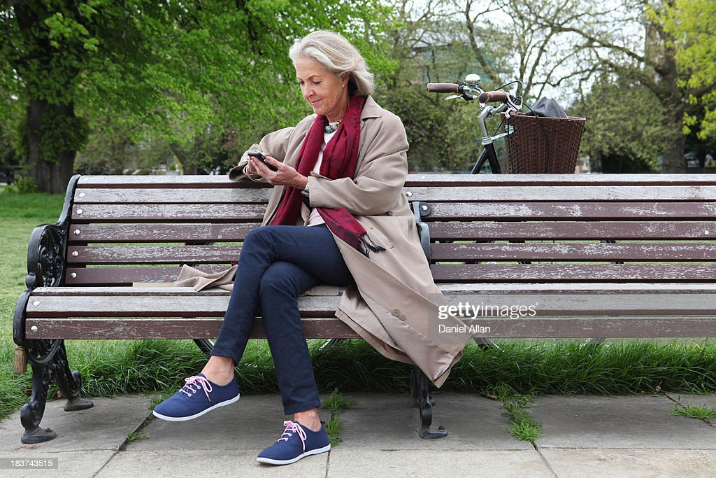 Senior woman sitting on park bench and looking at mobile phone