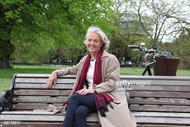 Senior woman sitting on park bench, portrait
