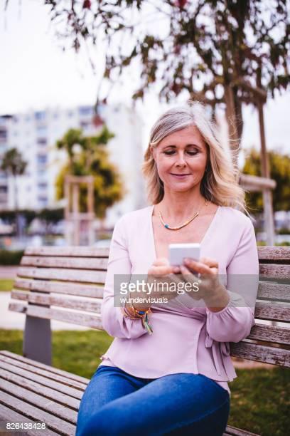 Senior Frau sitzt auf Park Bench SMS auf Smartphone