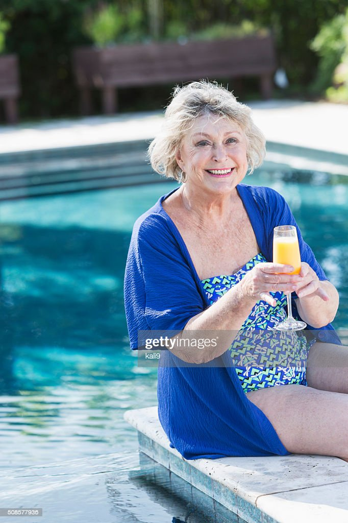 Senior woman sitting on pool deck with drink : Stockfoto