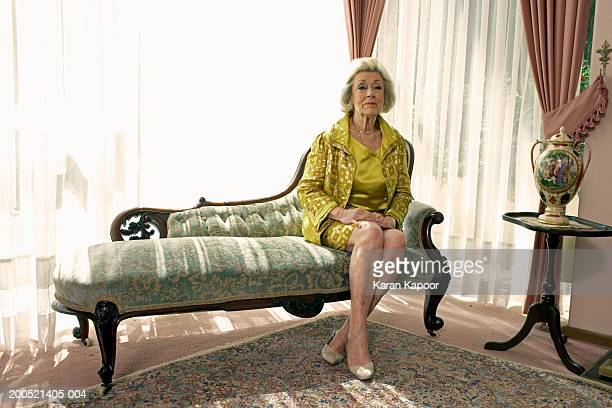 Senior woman sitting on sofa, portrait
