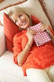 Senior Woman Sitting On Sofa Reading Diary