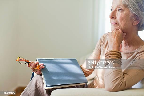 Senior woman sitting on sofa with book