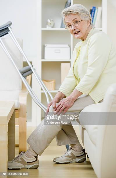 Senior woman sitting on sofa with crutches, holding knee, portrait