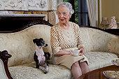 Senior woman sitting on sofa with dog, smiling