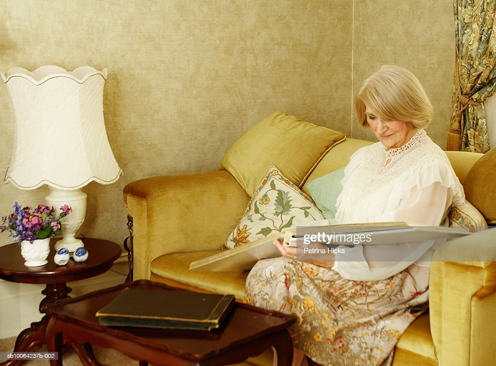Senior woman sitting on sofa with photo album : Stock Photo