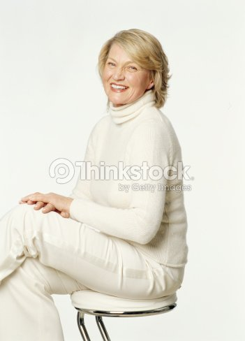 senior woman sitting on stool smiling portrait photo thinkstock. Black Bedroom Furniture Sets. Home Design Ideas