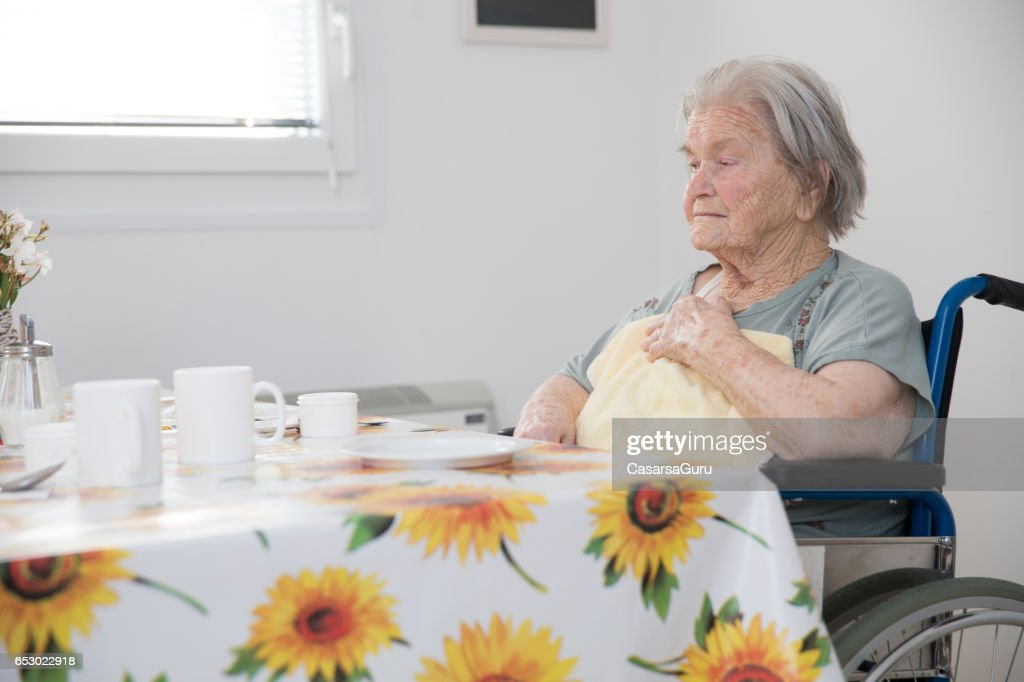 Senior Woman Sitting On The Wheelchair Waiting For Breakfast At The Care Center : Foto stock