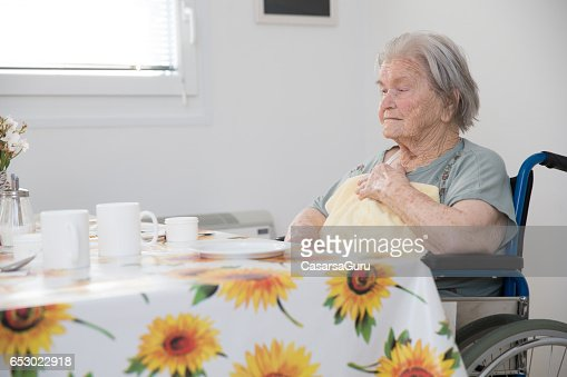 Senior Woman Sitting On The Wheelchair Waiting For Breakfast At The Care Center : Stock Photo