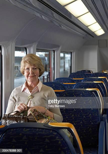 Senior woman sitting on train holding bags, smiling, portrait