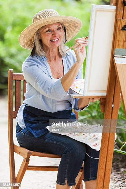 Senior woman sitting outdoors, painting