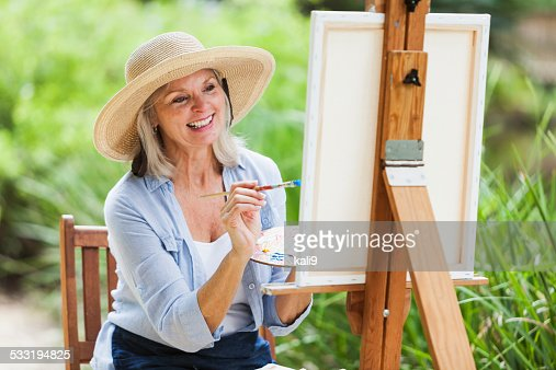 Senior woman sitting outdoors, painting