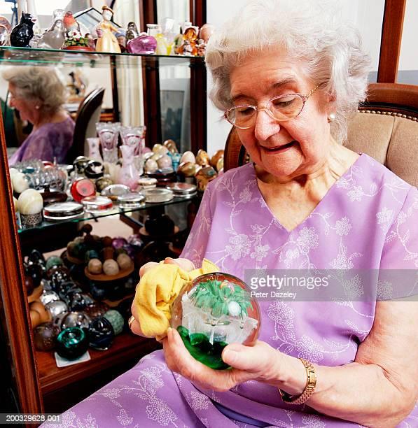 Senior woman sitting polishing paperweight, close up